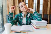 Schülerin beim Lernen, die mit nachdenklichem Blick nach oben schaut.