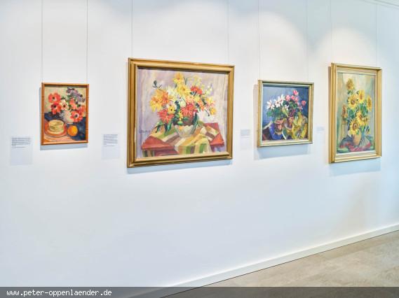 Vier Blumenstillleben an einer weißen Wand